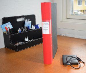 Digitaliserad bokföring innebär minskat antal bohyllor - bild på pärm och extern hårddisk. En självklarhet för Redovisningsbyrån i Helsingborg Solsnäckan AB.
